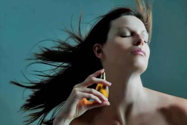 mujer perfumándose