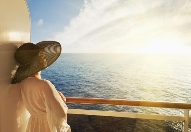 mujer con sombrero mirando el mar