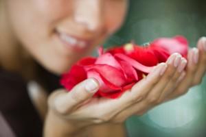 Mujer oliendo pétalos de flores