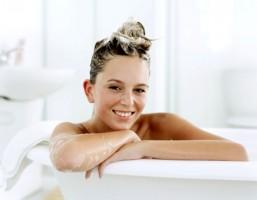 Mujer con mascarilla capilar en la bañera