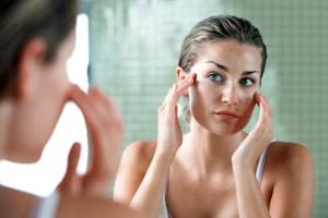 Mujer aplicándose crema delante del espejo