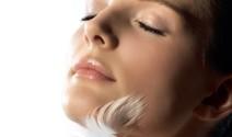 Mujer con pluma en la cara