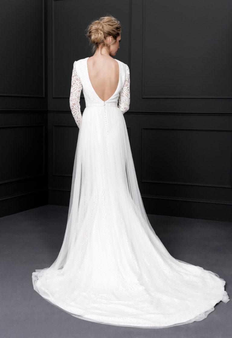 Este vestido manga larga elaborado en encaje rebrodé, también destaca con elegancia la espalda. Un diseño nupcial perfecto para una boda ideal con la falda de encaje con sobrefalda de tul de seda.